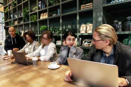 five people sitting near table using laptops inside room